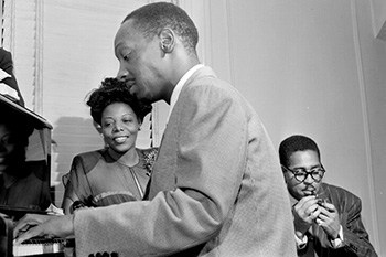 Tadd Dameron sentado al piano en compañía de Dizzy Gillespie.